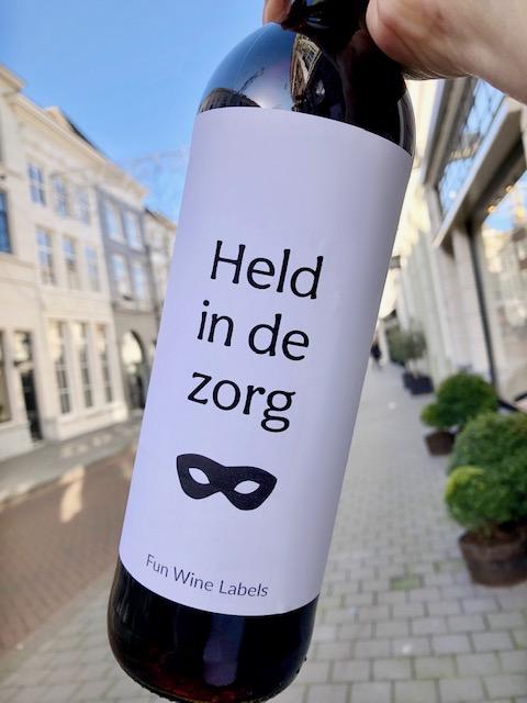 wijnetiket zorg held op een fles wijn